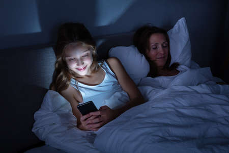Happy Girl Using Mobile Phone While Her Daughter Sleeping On Cozy Bed At Night