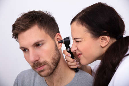 Female Doctor Examining Male Patients Ear With Otoscope Фото со стока