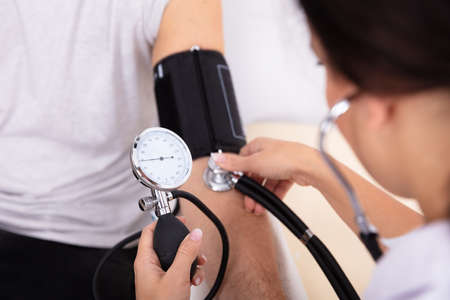 Close-up Of Doctor Measuring Blood Pressure Of Male Patient
