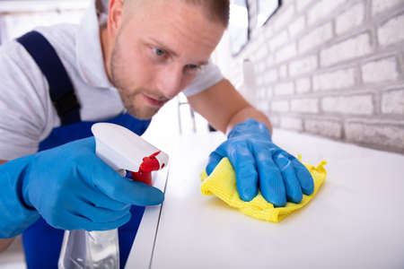 Close-up Of A Young Male Janitor Cleaning Furniture With Yellow Cloth