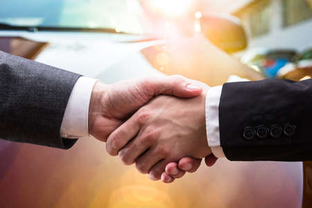 Two Businessmen Shaking Hands In Front Of Vehicle
