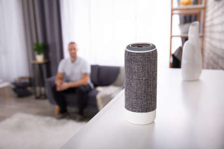 Close-up Of Wireless Speaker In Front Of Man Sitting On Sofa