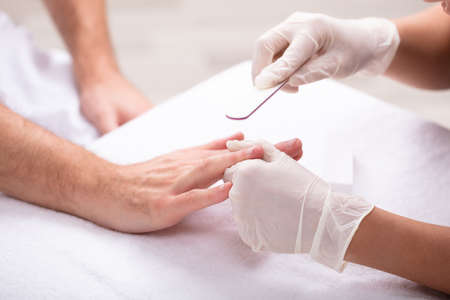 Close-up Of Beautician Manicure Nail Buff Of Man In Spa