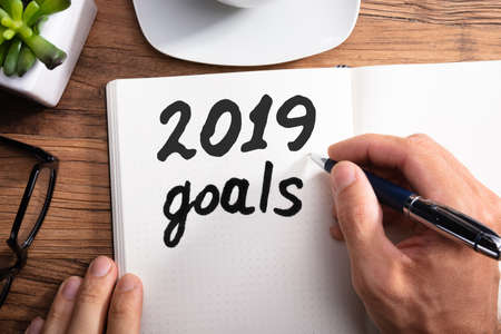 Close-up Of A Persons Hand Writing 2019 Year Goals On Dotted Notebook Over Wooden Desk