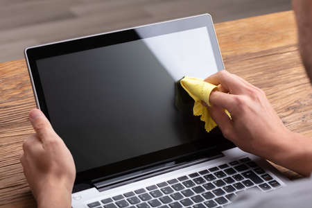 Man Cleaning Laptop Screen With Soft Yellow Cloth 免版税图像 - 113242073