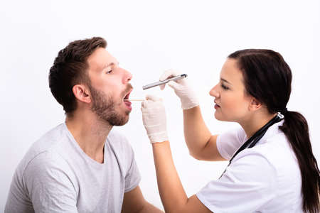 Young Female Doctor Checking Man's Sore Throat With Tongue Depressor