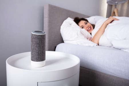 Smiling Young Woman Lying On Bed Listening To Music On Wireless Speaker