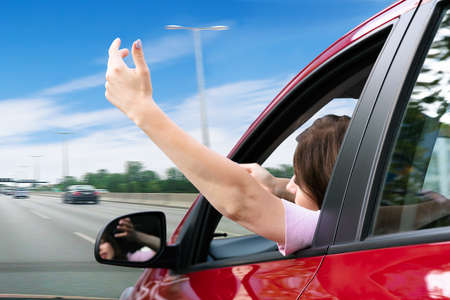 Young Woman Making Gesture While Looking Out Of Car Window