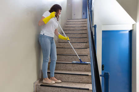 Young Female Janitor Cleaning Staircase With Mop Фото со стока