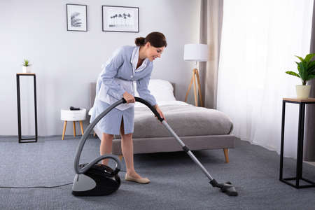 Happy Young Housekeeper Cleaning Carpet With Vacuum Cleaner In Hotel Room Фото со стока