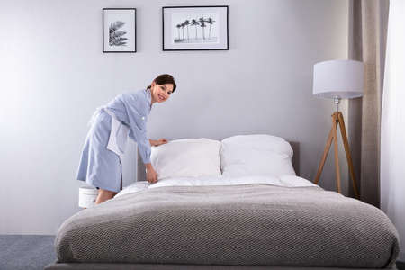 Smiling Female Housekeeper Making Bed In Hotel Room Stock Photo