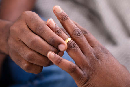 Close-up Of Man's Hand Putting Golden Engagement Ring On Woman's Finger