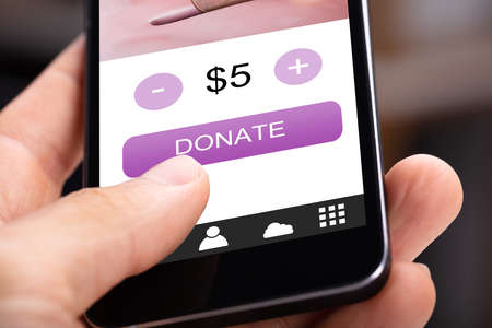 Close-up Of A Person's Hand Donating Money On Cellphone Archivio Fotografico - 115651344