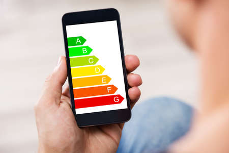 Close-up Of A Man's Hand Holding Cellphone With Energy Efficiency Chart On Screen Banque d'images