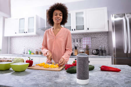 Wireless Speaker In Front Of Woman Cutting Vegetables On Chopping Board In The Kitchen Stock fotó - 115651347