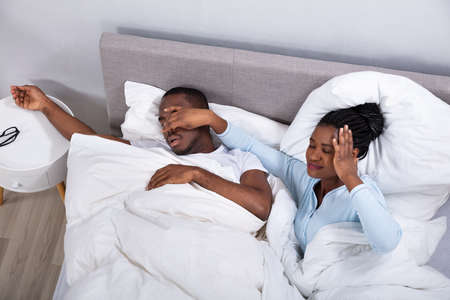 Disturbed Young African Woman Holding Her Husbands Nose To Stop Him From Snoring On Bed