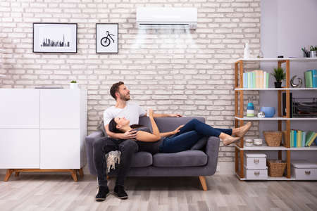 Happy Young Couple Sitting On Sofa Operating Air Conditioner At Home Reklamní fotografie
