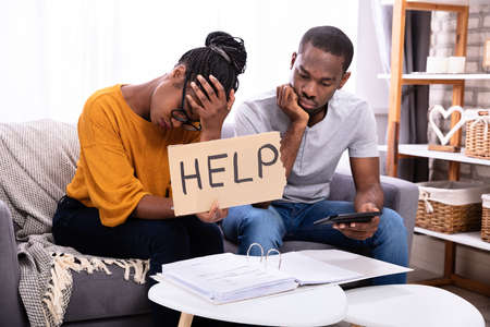 Young African Couple Sitting On Sofa Holding Help Sign While Calculating Bills