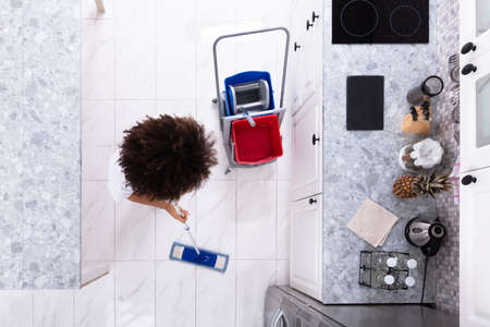 Female Janitor Cleaning The White Floor With Mop In Modern Kitchen 写真素材