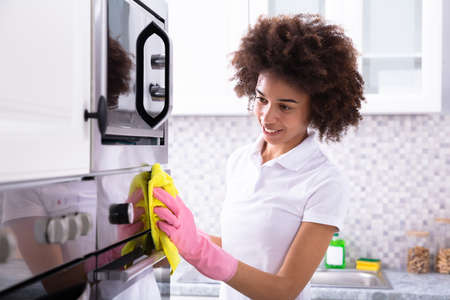 Close-up Of A Smiling Female Janitor Cleaning Oven With Yellow Napkin In The Kitchen Stock fotó