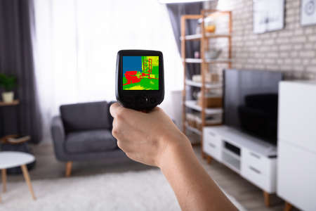 Womans Hand Using Infrared Thermal Camera To Check Temperature In Living Room