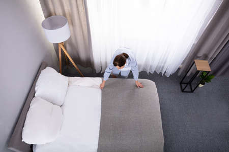Smiling Female Housekeeper Making Bed In Hotel Room Banco de Imagens