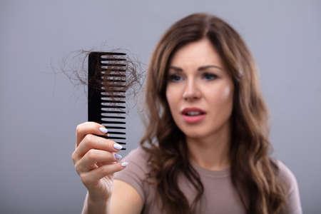 Close-up de una mujer preocupada sujetando el peine sufren de pérdida de cabello