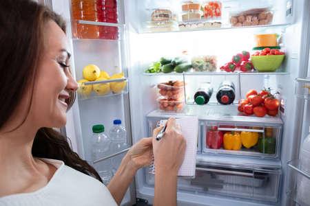 Close-up Of Happy Woman Writing On Spiral Book Near Open Refrigerator Фото со стока