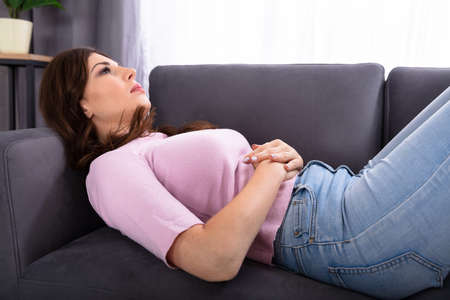 Young Woman Lying On Sofa Suffering From Stomachache At Home