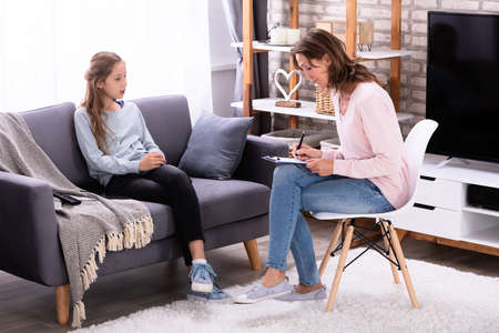 Girl Sitting On Sofa Explaining Her Problems To Female Psychiatrist At Home