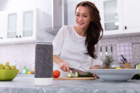 Happy Woman Talking To Voice Assistant While Slicing Cucumber With Kitchen Knife