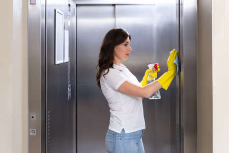 Side View Of A Smiling Young Female Janitor Cleaning Elevator With Duster 版權商用圖片