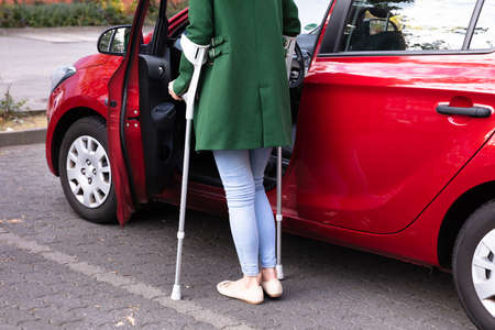 Disabled Young Woman With Crutches Opening Door Of A Red Car Stock fotó
