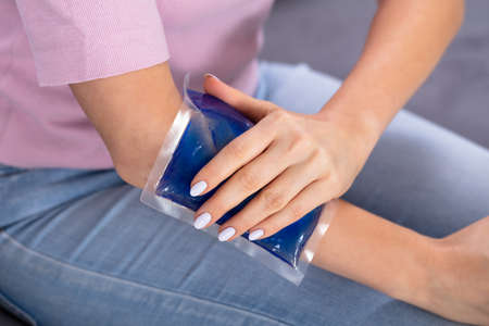 Close-up Of A Woman's Hand Using Ice Gel Pack On Arm