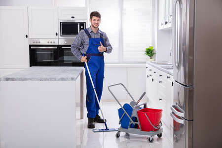 Male Janitor Cleaning Floor With Mop In Kitchen 写真素材