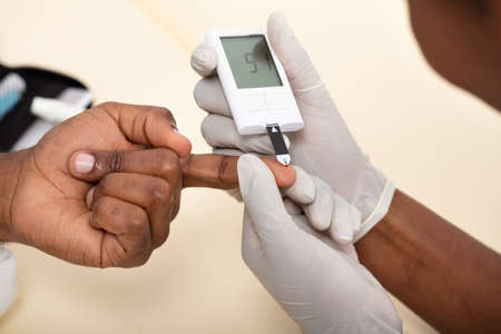 Close-up Of Female Doctor Checking Patient's Blood Sugar Level With Glucometer In Clinic
