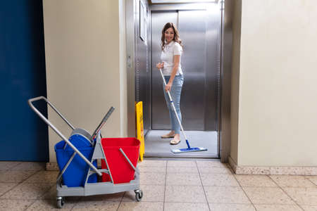 Happy Female Janitor Cleaning Elevator With Mop