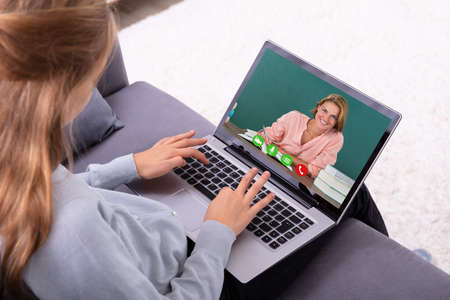 Close-up Of A Girl Video Conferencing With Happy Female Teacher On Laptop