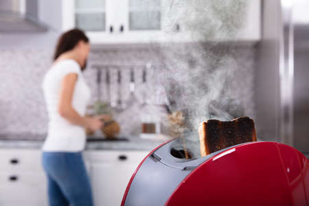 Close-up Of A Red Toaster With Burnt Toast While Woman Working In Kitchen Stok Fotoğraf
