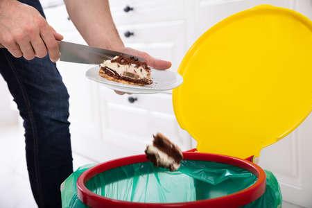 Close-up di una mano di uomo di gettare la torta nel cestino