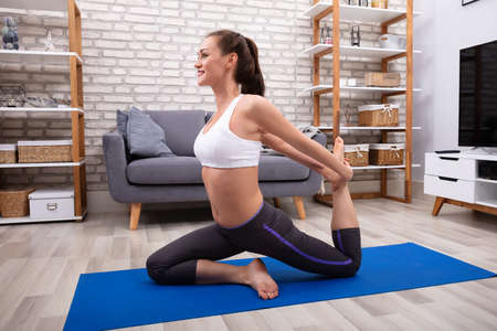 Side View Of A Happy Young Woman Doing Stretching Exercise On Blue Yoga Mat