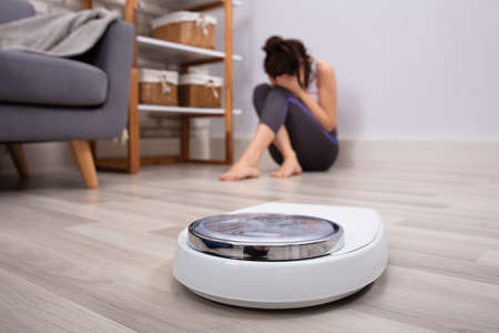 Close-up Of Weighing Scale In Front Of Sad Woman Sitting On Hardwood Floor