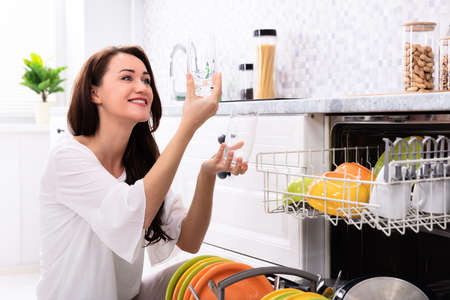 Happy Young Woman Looking At Drinking Glasses Near Dishwasher