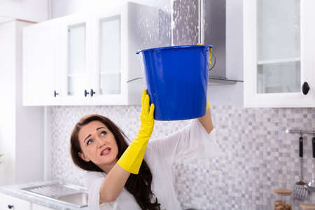 Unhappy Young Woman Collecting Water Leaking From Ceiling In Blue Bucket