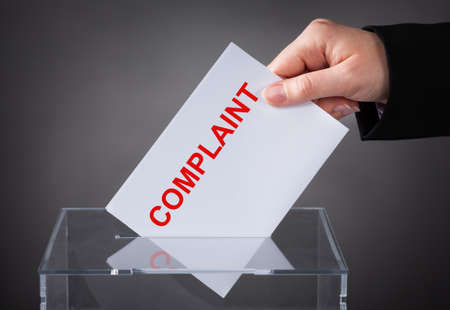 A Person's Hand Inserting Complaint Letter Into Box Slot On Grey Background