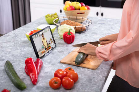 Woman Cutting Vegetables On Chopping Board In Front Of Digital Tablet On Kitchen Counter