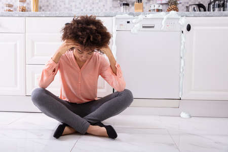 Worried Young Woman Sitting In Front Of Damaged Dishwasher With Foam Coming Out From It
