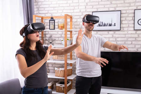 Young Couple Using Virtual Reality Device At Home