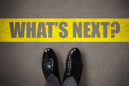 Persons Standing Next To Whats Next Text On Asphalt Background Stock Photo