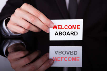 A Persons Hand Holding Welcome Aboard Card Stock Photo